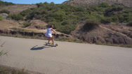 Stock Video Footage of AERIAL: Young woman longboarding on an empty road