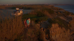 Young people watching sunset on top of the ocean cliff Stock Footage