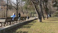 PRAGUE, CZECH REPUBLIC - People relax in the park, sits on a bench and walks - stock footage