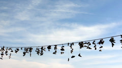 PRAGUE, CZECH REPUBLIC - MARCH 2014: Shoes hang on a rope Stock Footage