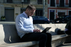 Businessman work on laptop and sit on street bench, steadycam shot. Stock Footage