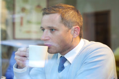 Pensive businessman drinking coffee in the cafe, steadycam shot. Stock Footage