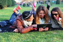 Happy women lying on blanket in park watch tablet and eat apple, steadycam shot. Stock Footage