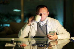 Doctor drinking coffee and using cellphone at night. Stock Footage