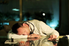 Doctor sleeping on the desk and switching off ringing cellphone. Stock Footage