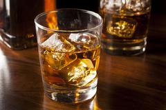 golden brown whisky on the rocks - stock photo