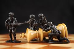 Toy soldiers kill chess King. - stock photo
