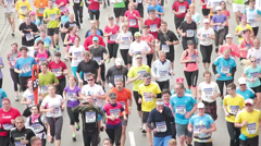 Large group of People running towards the camera at half Marathon event Stock Footage