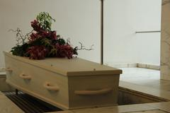 White casket with funeral flowers Stock Photos