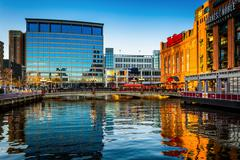evening reflections of buildings at the inner harbor in baltimore, maryland. - stock photo