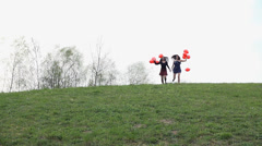 Two Girls With Red Balloons Running On Hill In Slow Motion Stock Footage