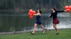 Two Young Ladies Enjoying Life At Lake With Red Balloons In Slow Motion Stock Footage