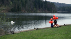 Girls With Red Balloons At Lake and Swan In Background Stock Footage