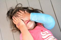 abused little girl with a broken arm - stock photo