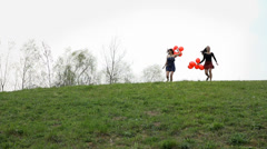 Two Attractive Woman Running Down The Hill With Red Balloons Stock Footage