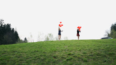 Wide Shot Of Two Women Throwing Red Balloons In To Air In Slow Motion Stock Footage