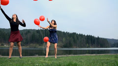 Two Older Girls Enjoying Playing With Red Balloons In Slow Motion Stock Footage