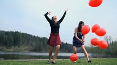 Two Women Enjoying Life At Lake Throwing Balloons In Air Stock Footage