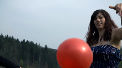 Close Up On Girl In Dress Playing With Red Balloons In Nature Stock Footage