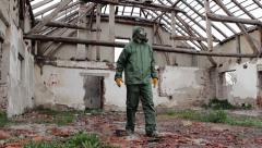 Man in decontamination suit  enters and explores in ruined building - stock footage