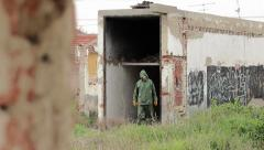 The man in decontamination suit in coming out from ruined building Stock Footage