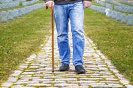 Stock Photo of Man with walking stick in cemetery