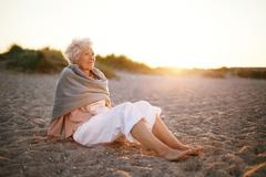 Relaxed elderly woman sitting on the beach Stock Photos