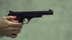 Angle on female hands holding and firing a pistol in slow motion - stock footage