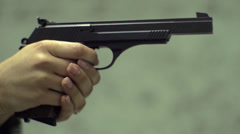 Female hands holding and firing a pistol in slow motion Stock Footage