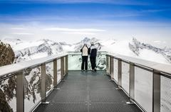 Two people looking at alps mountains from viewpoint platform Stock Photos