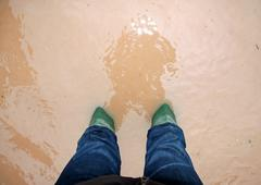 Green rescuer boots during a flood in the city Stock Photos