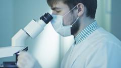 Doctor Doing Research, Looking through Microscope Stock Footage