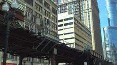 Metro train departure downtown Chicago suspension rail link cars passenger rail Stock Footage