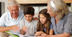 Grandparents chatting with grandchildren looking at photo album Stock Footage