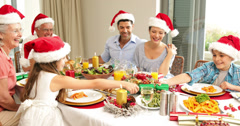 Siblings pulling a christmas cracker at the dinner table Stock Footage