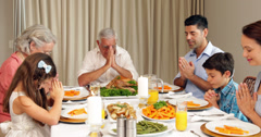 Extended family praying before dinner Stock Footage