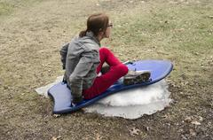 woman sledding on small amount of snow - stock photo