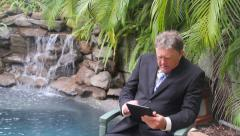 Businessman Walks And Sits By Waterfall Stock Footage