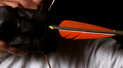 Man shooting an arrow on black background Stock Footage
