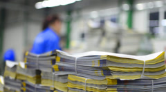 Dolly shoot of magazine print stuck in production line ready for delivery Stock Footage