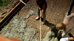 Concrete workers pouring concrete slab Stock Footage