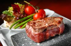 meat grilled on a stone with vegetables on the plate - stock photo