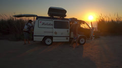 AERIAL: Young people getting out of surf van a sunset Stock Footage