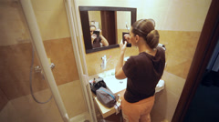 Beautiful woman mascaras her eyelashes in bathroom - stock footage