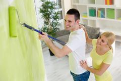 smiling couple painting hew home - stock photo
