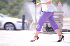 Violet trousers young adult woman walking crossing street Stock Footage