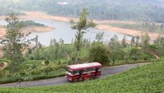 Bus traveling along road through tea plantation country Stock Footage