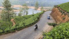 Motorbike passing tuk tuk motor taxi on rural road amongst tea plantation Stock Footage