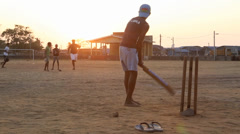 Teenage boys playing casual game of cricket using tennis ball at sunset Stock Footage