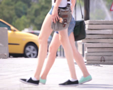 Two bluejeans shorts long naked legs young adult women walking Stock Footage